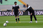 Head coach of Udinese Francesco Guidolin (R) speaks with Andrea Lazzari before between Udinese Calcio and Cagliari Calcio at Stadio Friuli on October 6, 2013 in Udine, Italy.