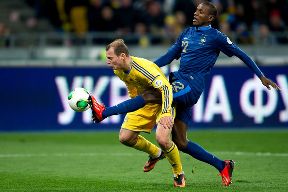 Roman Zozulya of Ukraine (L) fights for the ball with Eric Abidal of France (R) during the FIFA 2014 World Cup Qualifier Play-off First Leg between Ukraine and France at the Olympic Stadium on November 15, 2013 in Kiev, Ukraine.