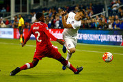 Cameron Carter #4 of the USA is tripped by Johnny Grant #2 of Canada during the 1st half of the 2015 CONCACAF Olympic Qualifying match at Sporting Park on October 1, 2015 in Kansas City, Kansas.