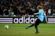 Diego Forlan of Uruguay scores the first penalty in a penalty shoot out during the 2010 FIFA World Cup South Africa Quarter Final match between Uruguay and Ghana at the Soccer City stadium on July 2, 2010 in Johannesburg, South Africa.