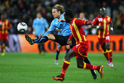 Diego Forlan of Uruguay controls the ball under pressure from Hans Sarpei of Ghana during the 2010 FIFA World Cup South Africa Quarter Final match between Uruguay and Ghana at the Soccer City stadium on July 2, 2010 in Johannesburg, South Africa.