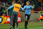 Diego Lugano congratulates Diego Forlan of Uruguay as he celebrates scoring his team's first goal from a free kick during the 2010 FIFA World Cup South Africa Quarter Final match between Uruguay and Ghana at the Soccer City stadium on July 2, 2010 in Johannesburg, South Africa.