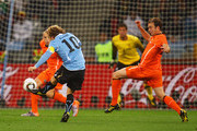 Diego Forlan of Uruguay shoots a long range effort and scores his team's first goal during the 2010 FIFA World Cup South Africa Semi Final match between Uruguay and the Netherlands at Green Point Stadium on July 6, 2010 in Cape Town, South Africa.
