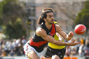 Jake Long of Essendon handballs whilst being tackled during the VFL Semi Final match between Richmond and Essendon at North Port Oval on September 8, 2018 in Melbourne, Australia.