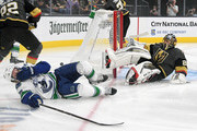 Antoine Roussel #26 of the Vancouver Canucks and Marc-Andre Fleury #29 of the Vegas Golden Knights fall to the ice in the first period of their game at T-Mobile Arena on October 24, 2018 in Las Vegas, Nevada.