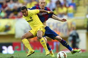 Giovani Dos Santos (L) of Villarreal competes for the ball with Mathieu of Barcelona during the La Liga match between Villarreal CF and FC Barcelona at El Madrigal stadium on August 31, 2014 in Villarreal, Spain.