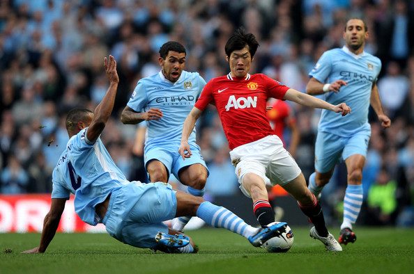 Vincent Kompany Ji-Sung Park of Manchester United is tackled by Vincent Kompany of Manchester City during the Barclays Premier League match between Manchester City and Manchester United at the Etihad Stadium on April 30, 2012 in Manchester, England.