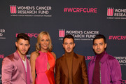 "(2nd from L) Jamie Tisch (L-R) Nick Jonas, Kevin Jonas, and Joe Jonas of The Jonas Brothers attends WCRF's ""An Unforgettable Evening"" at Beverly Wilshire, A Four Seasons Hotel on February 27, 2020 in Beverly Hills, California."