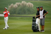 Liang Wen-chong of China (L) plays his approach to the 18th hole watched by Phil Mickelson of the USA during the final round of the WGC-HSBC Champions at the Sheshan International Golf Club on November 3, 2013 in Shanghai, China.