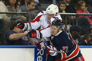 Ryan McDonagh #27 of the New York Rangers squeezes Joey Crabb #15 of the Washington Capitals into the boards at Madison Square Garden on February 17, 2013 in New York City.