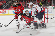 Keith Kinkaid #1 of the New Jersey Devils sweeps the puck away from Devante Smith-Pelly #25 of the Washington Capitals during the first period at the Prudential Center on October 11, 2018 in Newark, New Jersey.
