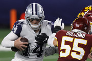 Andy Dalton #14 of the Dallas Cowboys under pressure from Cole Holcomb #55 of the Washington Football Team during the third quarter of a game at AT&T Stadium on November 26, 2020 in Arlington, Texas.
