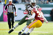 Chris Ivory #33 of the New York Jets stiff arms Trenton Robinson #34 of the Washington Redskins to gain extra yards during the third quarter at MetLife Stadium on October 18, 2015 in East Rutherford, New Jersey.