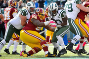 Chris Ivory #33 of the New York Jets escapes the tackle of Terrance Knighton #98 of the Washington Redskins and runs the ball for a first quarter touchdown at MetLife Stadium on October 18, 2015 in East Rutherford, New Jersey.