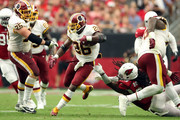 Running back Adrian Peterson #26 of the Washington Redskins slips by defensive back Tre Boston #33 of the Arizona Cardinals during the third quarter at State Farm Stadium on September 9, 2018 in Glendale, Arizona.