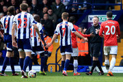 Referee Jonathan Moss signals to Youssuf Mulumbu (21) and James Morrison of West Bromwich Albion (7) and Patrice Evra (3R) and Robin van Persie of Manchester United (20) during the Barclays Premier League match between West Bromwich Albion and Manchester United at The Hawthorns on March 8, 2014 in West Bromwich, England.