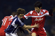 Billy Jones of West Bromwich Albion tangles with Ji-Sung Park of Queens Park Rangers during the FA Cup third round replay between West Bromwich Albion and Queens Park Rangers at The Hawthorns on January 15, 2013 in West Bromwich, England.