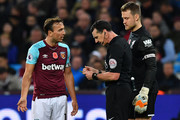 West Ham United's English midfielder Mark Noble (L) receives a yellow card during the English Premier League football match between West Ham United and Liverpool at The London Stadium, in east London on November 4, 2017. / AFP PHOTO / Ben STANSALL / RESTRICTED TO EDITORIAL USE. No use with unauthorized audio, video, data, fixture lists, club/league logos or 'live' services. Online in-match use limited to 75 images, no video emulation. No use in betting, games or single club/league/player publications.  /