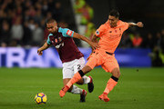 Winston Reid of West Ham United and Roberto Firmino of Liverpool battle for possession during the Premier League match between West Ham United and Liverpool at London Stadium on November 4, 2017 in London, England.