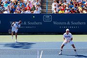 Mardy Fish and Mark Knowles of the Bahamas serve against Gael Monfils of France and Philipp Kohlschreiber of Germany during Day 1 of the Western & Southern Financial Group Masters at the Lindner Family Tennis Center on August 16, 2010 in Cincinnati, Ohio.