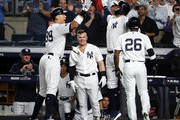 Aaron Judge #99 of the New York Yankees celebrates with Aaron Hicks #31 and Andrew McCutchen #26 after hitting a two run home run in the first inning against the Oakland Athletics during the American League Wild Card Game at Yankee Stadium on October 03, 2018 in the Bronx borough of New York City.