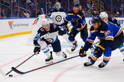 Joshua Morrissey #44 of the Winnipeg Jets and Ryan O'Reilly #90 of the St. Louis Blues race to a loose puck at the Enterprise Center on October 4, 2018 in St. Louis, Missouri.