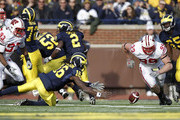 Denard Robinson #16 of the Michigan Wolverines tries to beat J.J. Watt #99 of the Wisconsin Badgers to a fumble at Michigan Stadium on November 20, 2010 in Ann Arbor, Michigan. Wisconsin won the game 48-38.