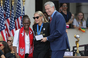 """Allie Long of the United States Women's National Soccer Team receives the key to the city from Chirlane McCray (l) and Mayor Bill de Blasio during a ceremony at City Hall on July 10, 2019 in New York City. The honor followed a ticker tape parade up lower Manhattan's """"Canyon of Heroes"""" to celebrate their gold medal victory in the 2019 Women's World Cup in France."""