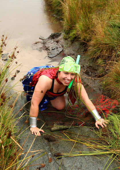 Mia Roberts of North Wales climbs out of the bog as she completes the 120yd course dressed as Wonder Woman during the World Bog Snorkelling Championships held at Waen Rhydd Bog on August 31, 2009 in Llanwrtyd Wells, Wales.