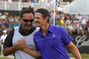 Justin Rose of England and caddie Mark Fulcher celebrate winning the World Golf Championship's Cadillac Championship at Doral Golf Resort And Spa on March 11, 2012 in Miami, Florida.
