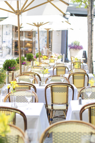 The sprawling sidewalk dining area features traditional table settings accompanied by rattan bistro chairs.