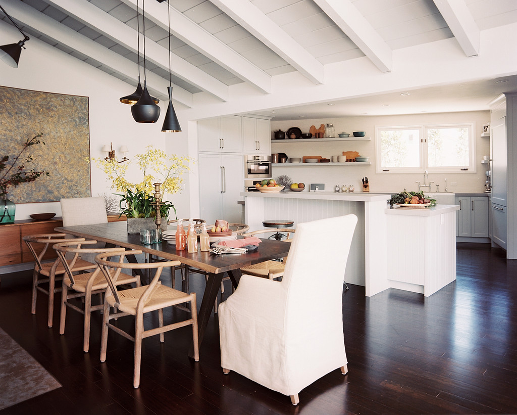 A kitchen and dining area with stained wood floors | Lonny