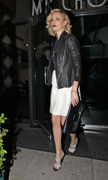 Charlize Theron toughened her color-block cocktail attire with a classic black leather jacket.