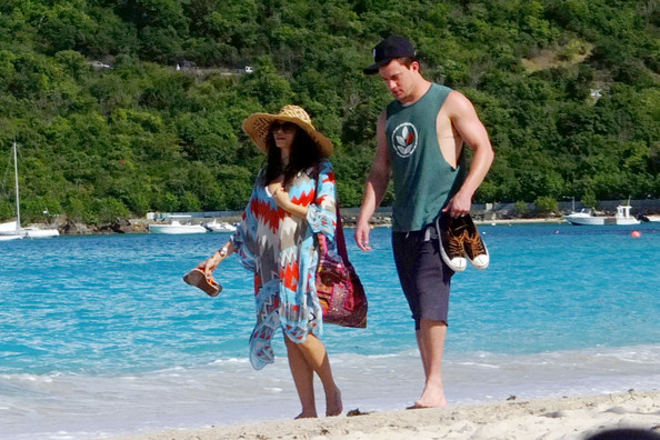 """Channing Tatum and pregnant wife Jenna Dewan hold hands as they go for a romantic stroll along the beach in the French West Indies. The """"Magic Mike"""" actor wore a muscle shirt, baseball cap, and shorts while his wife covered up her baby bump and bikini in a colorful sarong."""