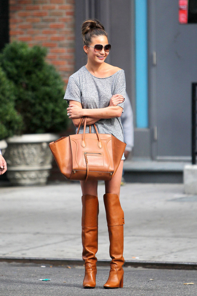 Chrissy Teigen, wearing knee-length brown leather boots with grey top and blue denim hot pants, hails a NYC taxi.