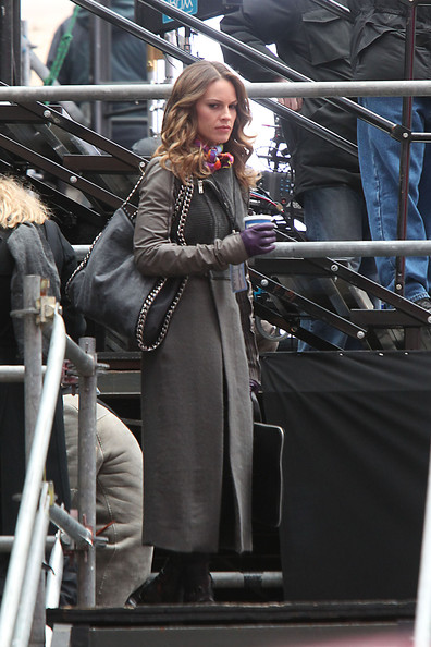 "Hilary Swank waves to a group of onlookers while hanging out on the set of her upcoming film ""New Year's Eve"", filming on location in Times Square. Wearing purple gloves, Swank could be seen holding onto a cup of coffee before filming a scene."