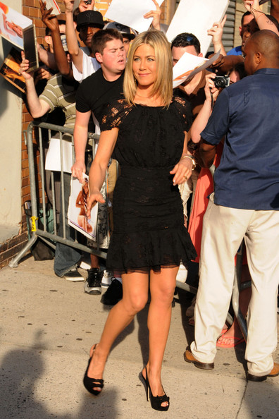 "Jennifer Aniston poses for pictures and signs autographs in a little black dress ahead of an appearance on ""The Daily Show with Jon Stewart.""  The actress, who is currently rumoured to be engaged to actor Justin Theroux, wears a diamond ring on her right hand and a gold ring on her left ring finger."