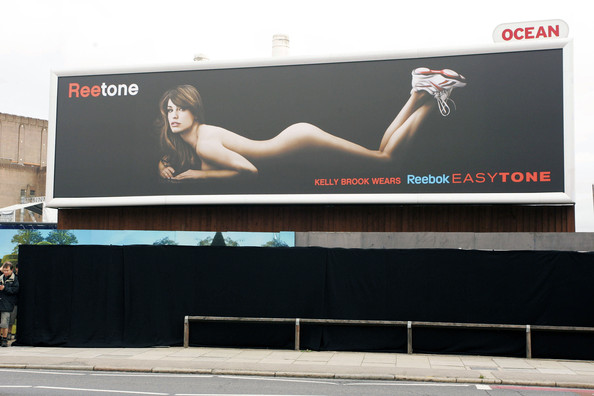 Kelly Brook attracts a LOT of attention in London as she unveils her near-naked poster for Reebok EasyTone shoes.
