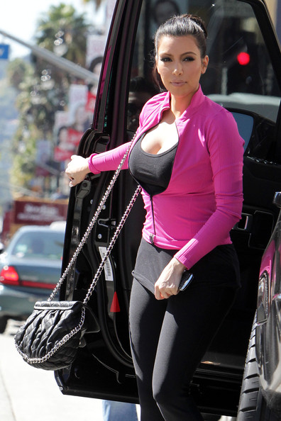 Kim Kardashian Kim Kardashian is followed by a camera crew as she arrives at the International Dance Academy in Hollywood. Kim, who was dressed in her best workout gear, wore a hot pink zip up jacket, low cut black tank top, skin tight black pants and pink athletic shoes.