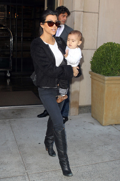Kourtney Kardashian holds onto her son Mason as she leaves her New York City hotel with her sister Kim. The sisters reportedly hopped into a SUV which was loaded with their luggage.