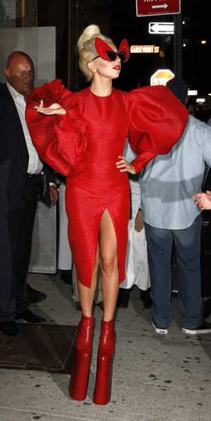 Lady in Red! Gaga shows off a little more than she'd hoped in a red crotch revealing outfit as she leaves a photoshoot in New York. The pop superstar was dressed in typically flamboyant style - sporting Dame Edna Everage-esque glasses, towering heel-less platforms and a red dress with huge puff sleeves.  Her stylist may have considered using some of the material from the voluminous sleeves to cover her modesty - as the thigh split showed off her own 'little monster'.