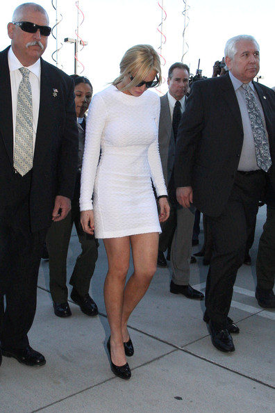 Lindsay Lohan Wearing a figure hugging white dress and dark sunglasses, Lindsay Lohan hangs her head as she is escorted into the Airport Courthouse for her arraignment on felony theft charges.