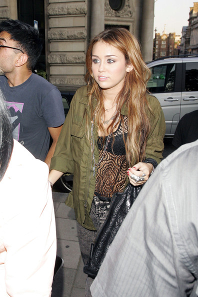 Miley Cyrus Miley Cyrus arrives for an appearance at a Topshop in central London where she ended up staying from 9:30 pm to 12 am. Miley was wearing a rather revealing black macrame top, acid wash jeans and high heels. She arrived back at her hotel around 12:30 am where she was greeted by a mob of fans.