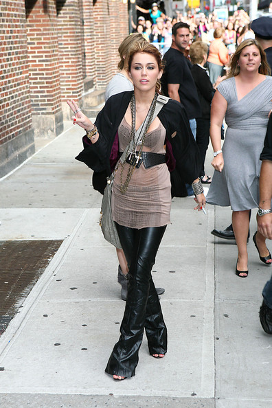 Miley Cyrus Miley Cyrus holds up the peace sign as she poses for photographs after appearing on