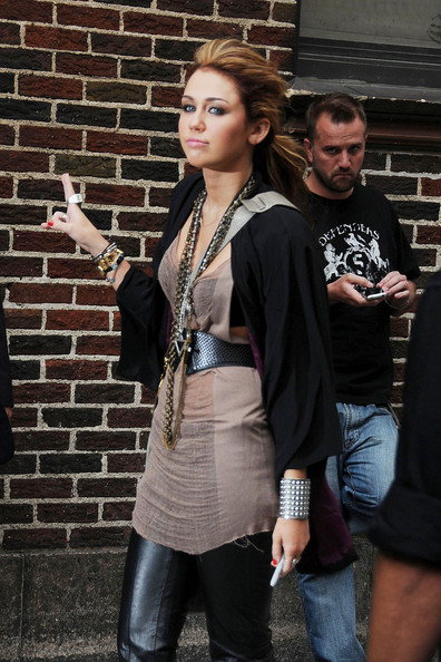 Miley Cyrus Miley Cyrus shows off a barely there beige top and a barrage of necklaces as she heads to make her appearance on the