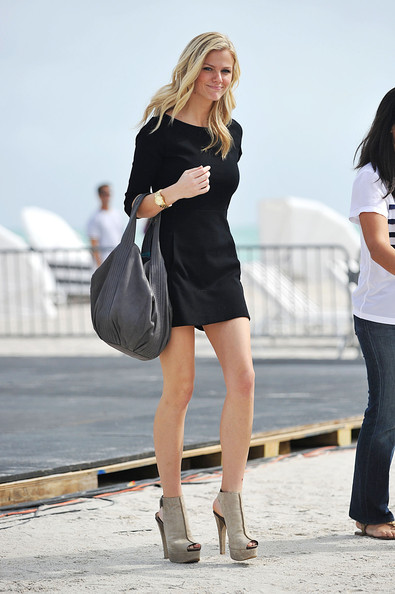 "February 5, 2010. Model Brooklyn Decker, Andy Roddick's wife, tries not to topple in the sand in her high heels after visiting the ""Dan Patrick Show"" in South Beach, FL. The Sports Illustrated model was looking lovely in a leggy black dress and a pair of beige suede peep-toe platform boots."