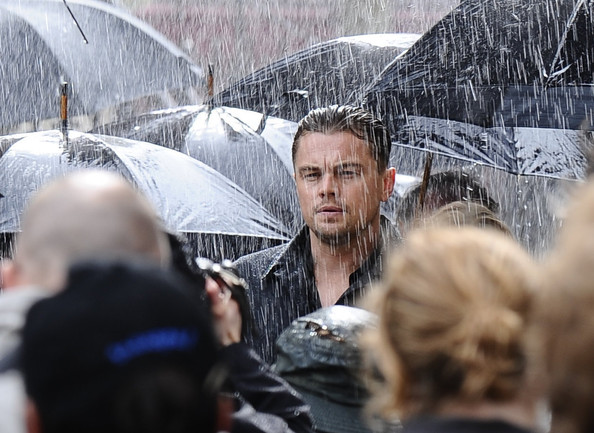 Rain man!  Leonardo DiCaprio on the very wet set for a new advertisement in Paris.  The actor is seen filming a commercial for Chinese mobile phone company Guandong OPPO Mobile Telecommuncations Corp and is reportedly  earning a tidy $5 Million for it.