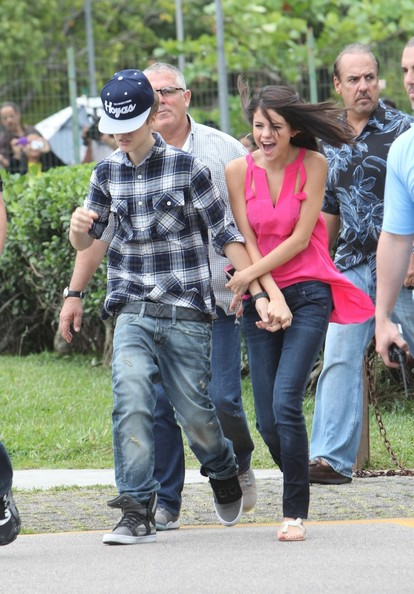 Selena Gomez Superstar couple Justin Bieber and Selena Gomez are escorted by security on their way to a helicopter ride in Brazil. Bieber sports a Georgetown Hoyas hat and covers his face a the helicopter picks up wind.