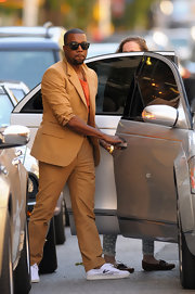 Kanye West showed off his carmel colored suit while heading out in Soho.