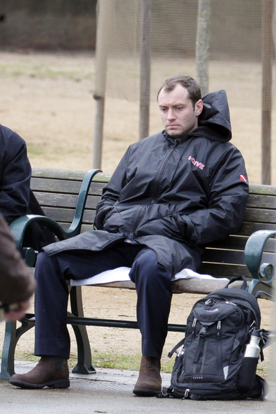 "A glum looking Jude Law films a scene for his upcoming film ""Contagion""  in San Francisco. The actor is seen sitting on a park bench, wearing a waterproof coat - before being handcuffed and ushered away. Law is seen sporting a fake front tooth."